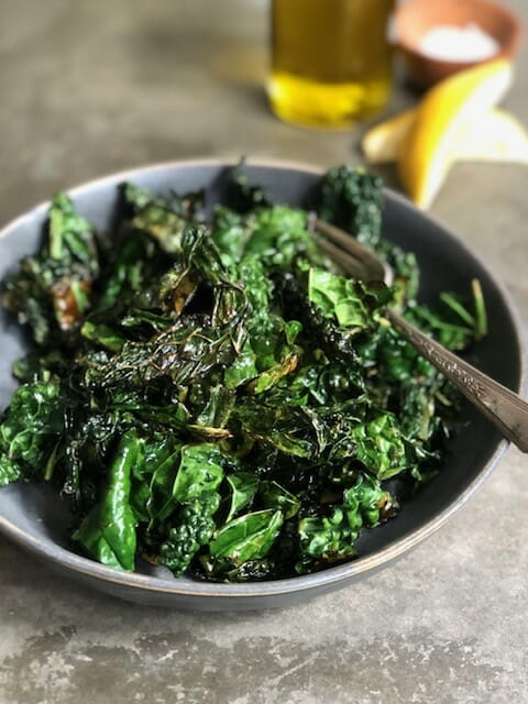 bowl of sauteed kale with olive oil, lemon, and salt
